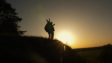 Hiker Girl Raising Her Hand Up, Celebrating Victory And Enjoying Scenery. mom and daughter on vacation traveling and dancing on mountain. Woman with raised hands on top of mountain looking at sunset.