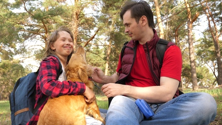 Happy family with a dog and children in a camping trip. Carefree teenagers with their father on a day off. Hiking. Vacation. A dog breeder with a dog and children for a walk. Stock Photo