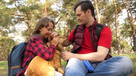 Happy family with a dog and children in a camping trip. Carefree teenagers with their father on a day off. Hiking. Vacation. A dog breeder with a dog and children for a walk. Banco de Imagens