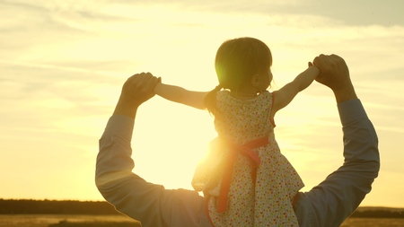 father walks with his daughter on his shoulders in rays of sunset. Dad carries on shoulders of his beloved child, walking across field. A baby with parents walks in evening at sunset. Slow motion.