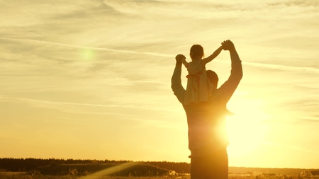 Dad dancing on his shoulders with his daughter in sun. Father travels with baby on his shoulders in rays of sunset. A child with parents walks at sunset. happy family resting in park. family concept