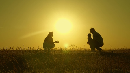 mother and Dad play with their daughter in the sun. happy baby goes from dad to mom. young family in the field with a child 1 year. family happiness concept. beautiful sunshine, sunset.