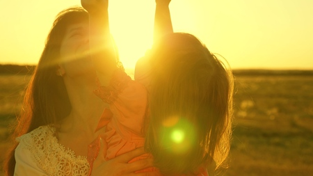 happy mother walks with her daughter in her arms in the rays of the sunset. Mom is talking with happy baby, baby is sitting on mothers arms at sunset of the golden sun. Slow motion.