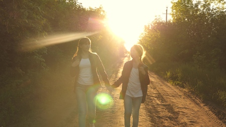 children travelers. teen girls travel and hold hands. Hiker Girl. girls with backpacks are on the country road in the sun. concept of sports tourism and travel. Banco de Imagens