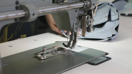 process of sewing leather goods. The needle of the sewing machine in motion. two needles of the sewing machine quickly moves up and down, close-up. Tailor sews black leather in a sewing workshop.