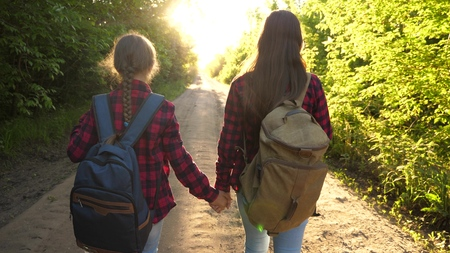 Hiker Girl. girls travel with backpacks on a country road. women tourists go to the sunset. Happy family on vacation travels. sports tourism concept. Banco de Imagens