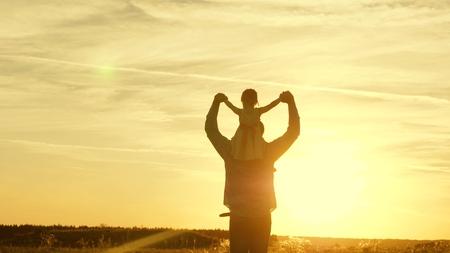 태양 아래 그의 딸과 함께 그의 어깨에 아빠 춤. 아버지는 일몰 광선에 그의 어깨에 아기와 함께 여행합니다. 부모와 함께 아이가 석양에 걷는다. 공원에서 쉬고 있는 행복한 가족. 가족 개념 스톡 콘텐츠