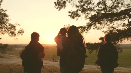 women travel, walk through forest, admire scenery at sunset. Hiker Girl. Tourists rejoice and raise their hands up. travelers mom and travel with backpacks. Family on vacation traveling with a child.