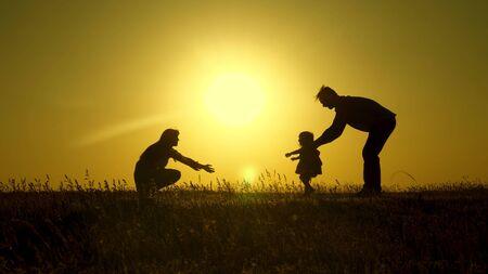 Eltern spielen mit ihrer kleinen Tochter. Mutter und Vater spielen mit ihrer Tochter in der Sonne. Happy Baby geht von Papa zu Mama. junge Familie im Feld mit einem Kind 1 Jahr. Familienglück Konzept.