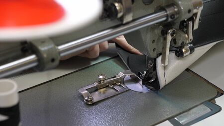 needle of the sewing machine quickly moves up and down. process of sewing leather goods. Tailor sews black leather in sewing workshop. needle of the sewing machine in motion, close-up.
