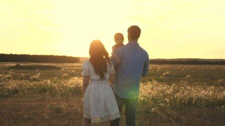 Famiglia che gioca con la figlia al sole. bambino felice seduto sulle mani dei genitori. Mamma e papà giocano con la loro piccola figlia nel parco al tramonto. passeggiata in famiglia con il bambino nel parco.
