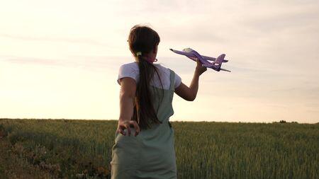 Glückliches Mädchen läuft mit einem Spielzeugflugzeug auf einem Weizenfeld. Kinder spielen Spielzeugflugzeug. Teenager träumt davon zu fliegen und Pilot zu werden. das Mädchen möchte Pilotin und Astronautin werden.