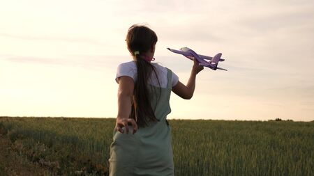 Happy girl runs with a toy plane on a wheat field. children play toy airplane. teenager dreams of flying and becoming a pilot. the girl wants to become a pilot and astronaut.