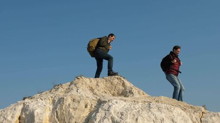 traveler overcomes a mountain pass. three climbers climb one after the other on a white rock. teamwork of business people. Team traveler goes to victory and success.