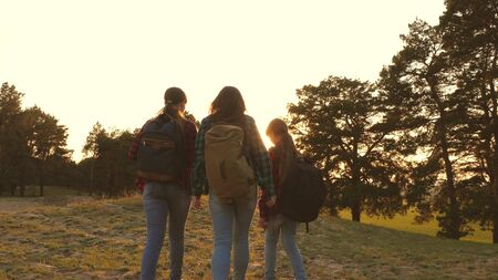 Hiker Girl. three girls travel, walk through woods to climb hill rejoice and raise their hands to the top. girls travel with backpacks on country road. Happy family on vacation travels.