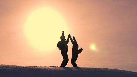 Tourists come to top of snowy hill and rejoice at victory against backdrop of a yellow sunset. travelers met on top of success. teamwork and victory. ecological tourism 版權商用圖片
