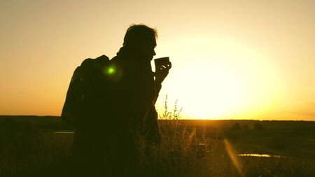 traveler drinks hot tea and watches sunset. rest after reaching the goal. lonely tourist sitting on top of hill drinking coffee . concept of freedom and dreams. world without borders 版權商用圖片