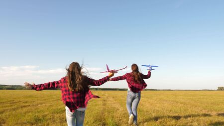 children play toy airplane. teenagers want to become pilot and astronaut. Happy girls run with toy plane at sunset on field. concept of a happy childhood. Girls dream of flying and becoming a pilot.