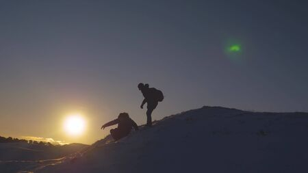 Silhouettes of men descending from high snowy mountain seeking adventure in glare of setting sun in winter. Concept of climbers who conquered mountain.Teamwork. Friends visiting terrain of mountains