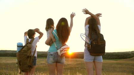 Mom travels with her daughters, admire the sunset and wave their hands. Mom and children are tourists. girls travel in the sunset light. Hiker Girl. girls travel with backpacks on a country road.