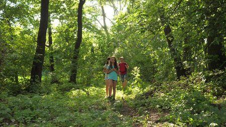 Papa und Töchter, Kinder reisen im Sommer im Park. Familie im Urlaub reist im Wald. Freunde-Touristen gehen im Wald campen. Menschen gehen durch Bäume und Gras. Teamwork-Reisende