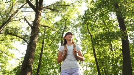 Hiker woman walks in the forest. Girl traveler is walking through the woods with a backpack. happy hiker girl in summer park. teenager girl adventures on vacation. Banco de Imagens