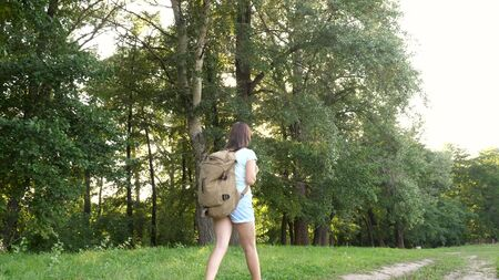 girl traveler with a backpack walks along a forest road. Hiker woman walks in the forest. happy hiker girl in summer park. teenager girl adventures on vacation.