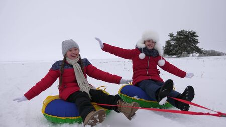 children slides in snow on an inflatable snow tube and waves hand. Happy girls slides through snow on sled. kids playing in park for the Christmas holidays in winter