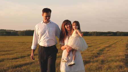 father and little daughter, mother, walking in a field in the sun. child, dad and mom play in the meadow in the sun. concept of a happy childhood. Happy young family. concept of a happy family.