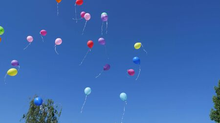 beautiful helium balloons fly through the air. Many colorful balloons flying in the air. holiday concept Stock Photo