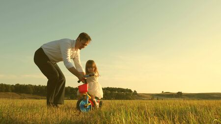 happy father teaches little daughter to ride a bike. Dad plays with small child on lawn. kid learns to ride bicycle. parents and little daughter walks in park. concept of happy family and childhood. Stock Photo