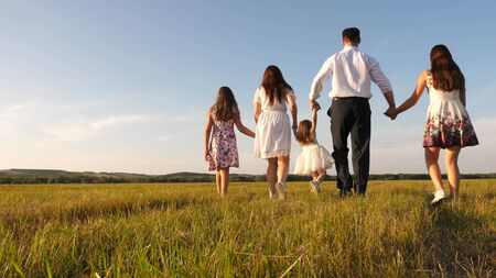 mother, father and little daughter with sisters walking in field in the sun. Happy young family. Children, dad and mom play in meadow in the sunshine. concept of happy family. Stock fotó