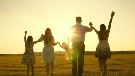 mother, father and little daughter with sisters walking in field in the sun. Happy young family. Children, dad and mom play in meadow in the sunshine. concept of a happy family.