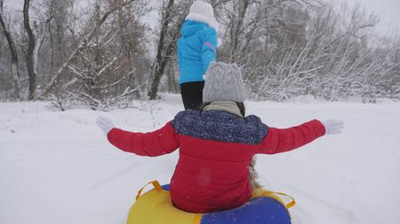 family winter vacation. child and mother sledding in snow. Daughter and mom play in the winter park on Christmas holidays. happy childhood concept