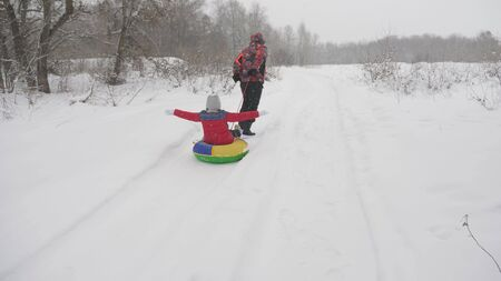 Happy dad sledges a child on a snowy road. Christmas Holidays. father plays with his daughter in a winter park. The concept of a happy family. teenager rides in Tubing