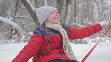 A happy girl rolls on Tubing along a white snowy road and laughs in a flight of freedom. Christmas Holidays. A fun game for adults and children. The concept of a happy family