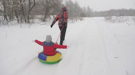 Happy dad sledges a child on a snowy road. Christmas Holidays. father plays with his daughter in a winter park. The concept of a happy family. teenager rides in Tubing Stock fotó - 133565957