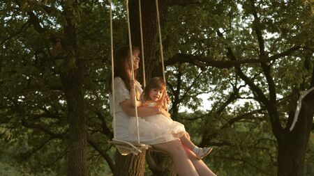 mother and baby ride on a rope swing on an oak branch in forest. Girl laughs, rejoices. Family fun in park, in nature. warm summer day. Mom shakes her daughter on swing under a tree in sun.