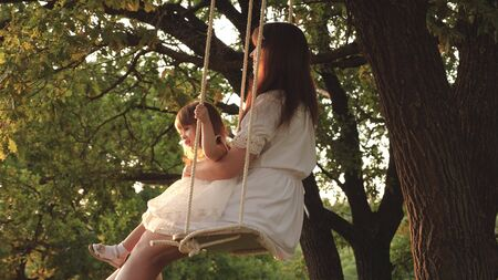 mother and baby ride on rope swing on an oak branch in forest. Girl laughs, rejoices. Family fun in park, in nature. warm summer day. Mom shakes her daughter on swing under a tree in sun. close-up. Stockfoto