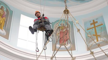 An industrial climber on a ladder is preparing a rope for lifting equipment. a worker in a protective helmet knits a knot on a rope.