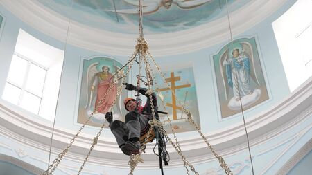 Industrial climber in equipment for high-altitude work working at high altitude in a church building. Climber high-altitude installation of a chandelier and lighting. on the climber s belt carabiners. Фото со стока