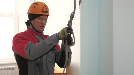 Industrial climber knits a rope for lifting equipment. a worker in a protective helmet knits a knot on a rope.