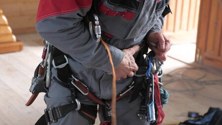 industrial climber puts on equipment for high-altitude work. on the climber s belt carabiners.