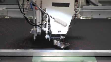 Robotics with cnc works in sewing a production line. Robot sewing machine. computer controls sewing machine. automatic sewing machine. Automated machine embroidery.
