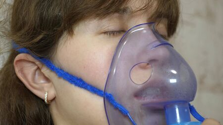 woman is treated with an inhalation mask on her face in a hospital. sick girl is inhaled by a nebulizer sitting on sofa. woman in mask. Inhale vapors for respiratory tract into lungs. Cough treatment