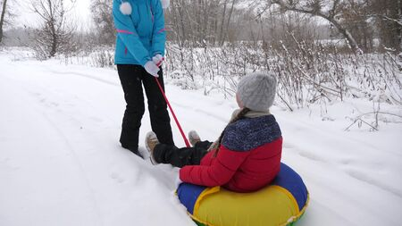 Happy mother rides a child on a sled on a white snowy road. Christmas Holidays. A fun game for adults and children. The concept of a happy family. A teenager rides in Tubing Standard-Bild