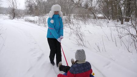 Happy mother rides a child on a sled on a white snowy road. Christmas Holidays. A fun game for adults and children. The concept of a happy family. A teenager rides in Tubing Фото со стока