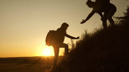 Tourists climb the mountain at sunset, holding hands. teamwork of business people. Traveler man holds out a womans hand to a traveler climbing to the top of the hill. Happy family on vacation. Фото со стока