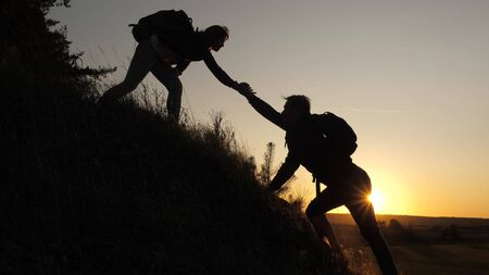 A male traveler holds out his hand to female traveler climbing a hilltop. Tourists climb the mountain in the sunset, holding hands. teamwork of business people. Happy family on vacation.