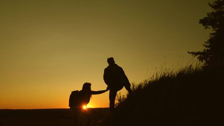 male traveler holds the hand of a female traveler helping to climb the top of the hill. Tourists climb the mountain at sunset, holding hands. team work of business partners. Happy family on vacation.
